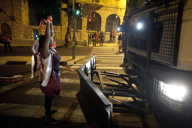An Ethiopian Israeli blocking a police vehicle in a protest against police brutality, in Jerusalem on April 30 CREDIT: Lior Mizrahi)