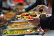 A man fills his plate in a buffet line.