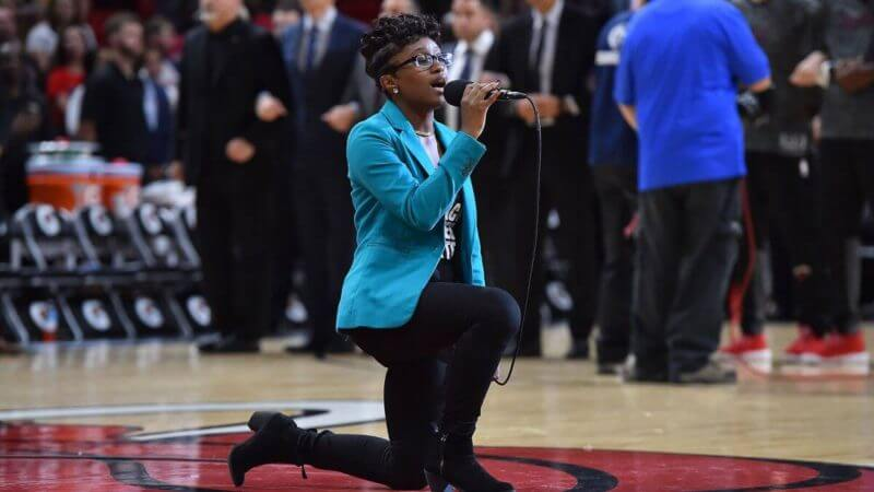 Woman kneels singing national anthem - Bent Corner