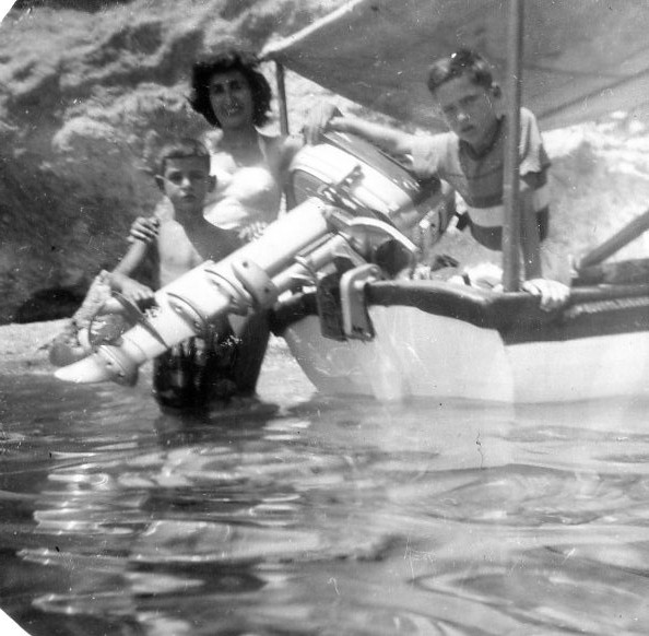 """Early seamanship exposure: here in Katramonisi of Voula, Byron with our Nanny and Nikos aboard """"BYRON"""", ca. summer of 1959."""