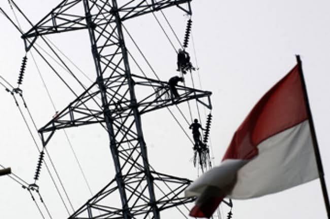 Petugas sedang melakukan pekerjaan di atas menara listrik tegangan ekstra tinggi