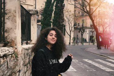 Görselde bir sokakta yüyürken arkama birden dönmüş olarak duruyorum. Sokak geniş ve ağaçlı, ağaçlar kuru ve yapraksız. Arkamda bir kilisenin arka duvarı var bej renkte ve dümdüz. Ben siyah kazaklıyım. Elim kabarık saçlarımda.