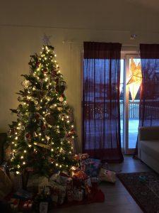 görselde pencere kenarında duran noel ağacı var. pencerenin solunda duruyor, boyu pencerenin tepesini geçiyor. apaç sarı küçük led ışıklarla aydınlatılmış ve kırmızı toplarla süslenmiş. altında ise hediye paketleri var.