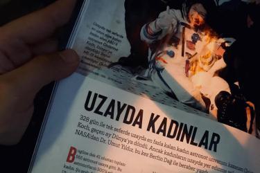 görselde, yazımızın dergi baskısının ilk sayfasından ufak bir fotoğraf var. foftoğrafta yazının başlığı olan UZAYDA KADINLAR görünüyor. üstünde ise net olmayan bir fotoğraf var, bir kadın astronot fotoğrafı. arkaplan beyaz, yazı ise siyah.