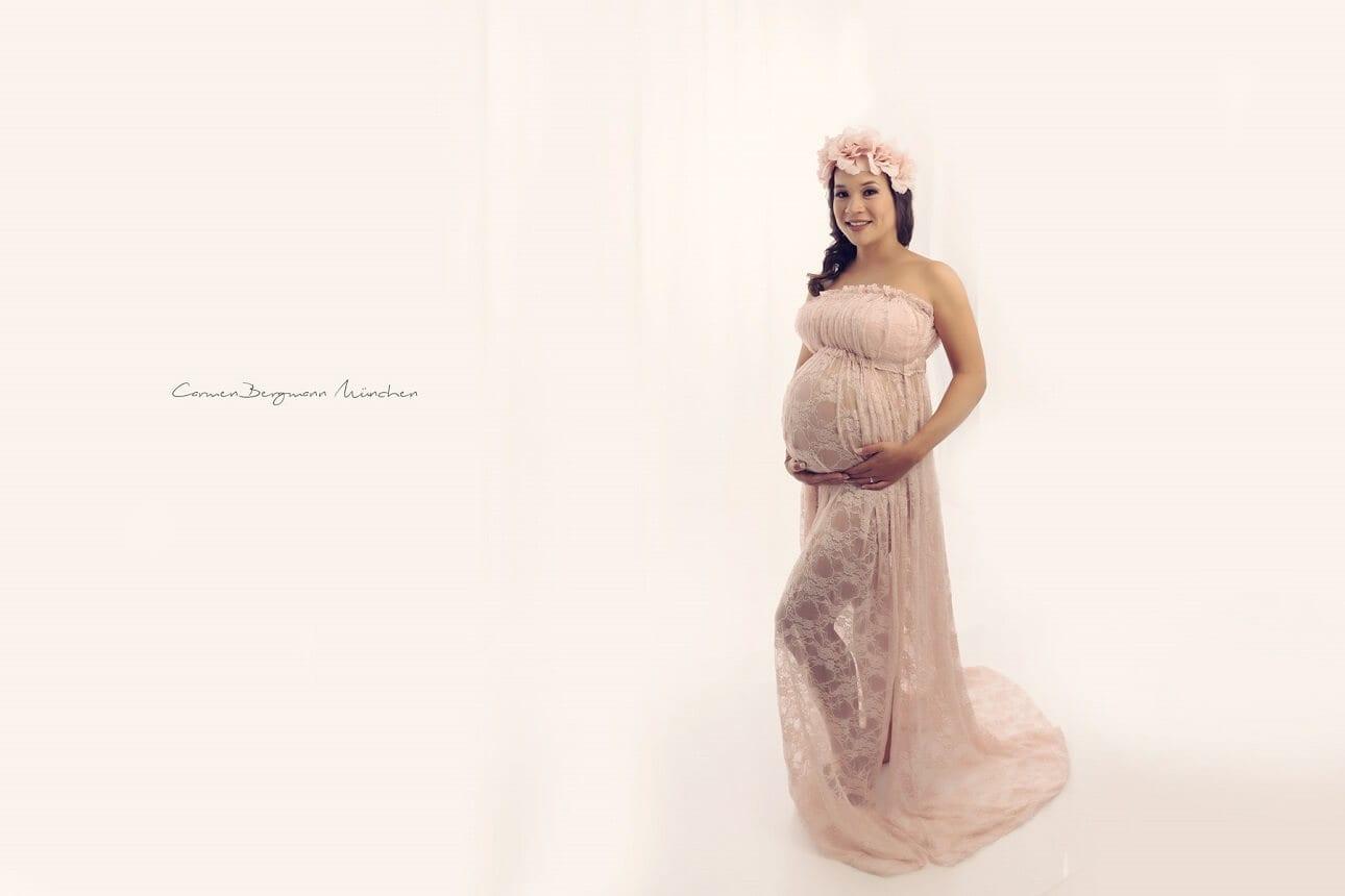Babybauch mit Kleid und Blumen im Haar in Fotostudio fuer schwangere in Muenchen