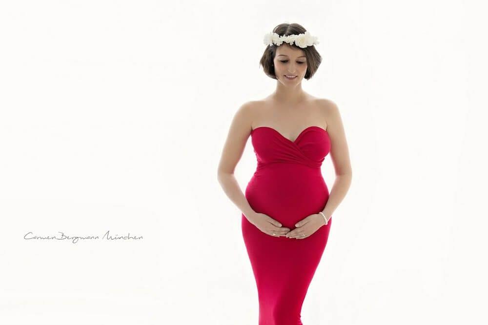 Bild einer schwangeren Frau in einem roten Babybauch Kleid im Fotostudio frontal aufgenommen mit Blumen im Haar