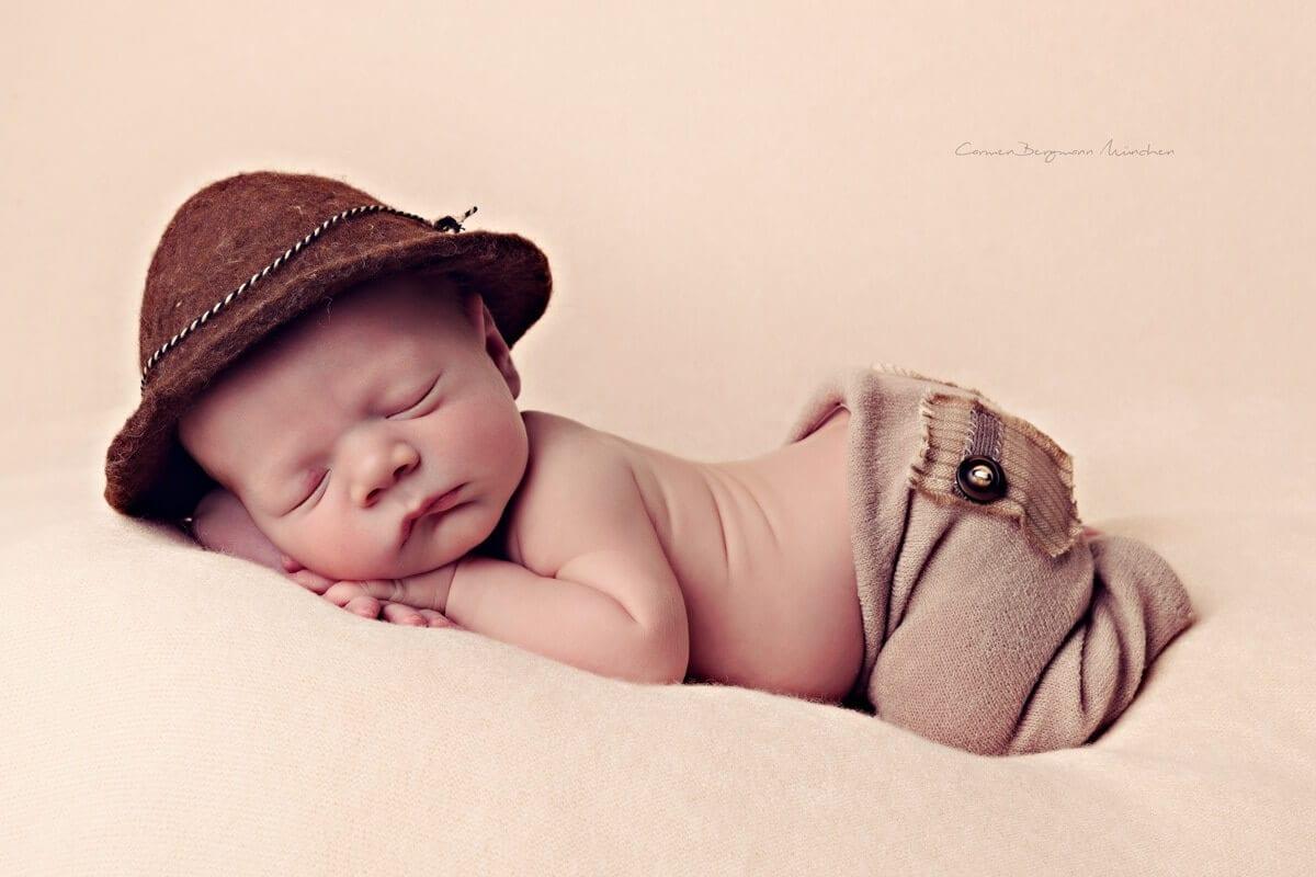 Neugeborenen Fotoshooting in Muenchen mit Hut auf Decke