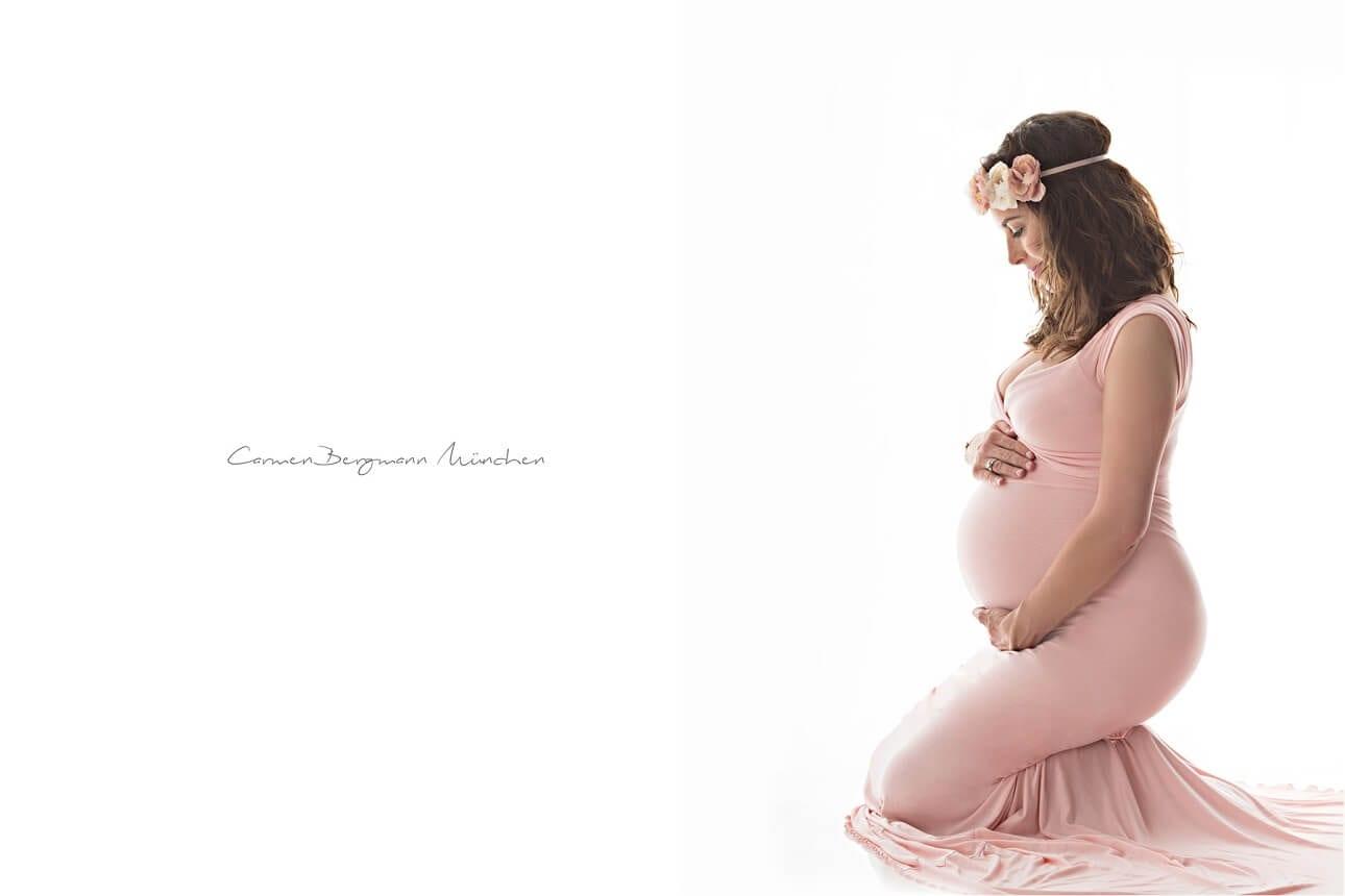 Schwangere kniet in Babybauch Fotostudio mit rosa Kleid von der Seite aufgenommen