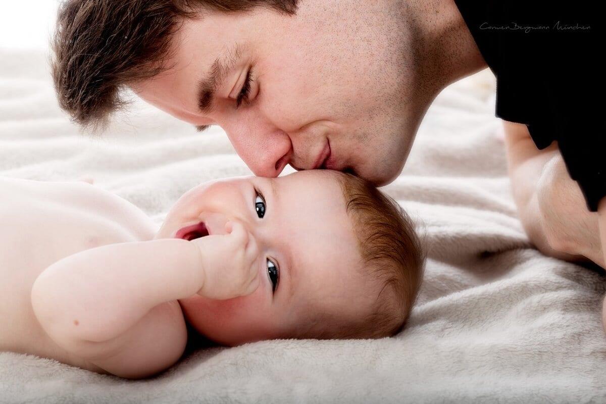 Vater kuesst Neugeborenes Kind auf Kopf in Fotostudio Neugeborenes lacht in Kamera