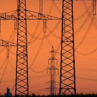 """ARCHIV - Die aufgehende Sonne taucht am 24.08.2017 den Himmel über einer Hochspannungsleitung bei Sehnde (Niedersachsen) in warmes Licht. Schleppender und teurer Netzausbau ist ein Lieblinsthema der Kritiker der Energiewende. Meist geht es dabei um die riesigen Stromtrassen quer durch Deut (zu dpa """"Große Netze, kleine Netze, oder:Wo spielt die Strom-Revolution?"""" vom 09.01.2018) Foto: Julian Stratenschulte/dpa +++(c) dpa - Bildfunk+++"""