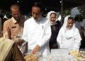 Presiden Joko Widodo (Jokowi) dan Ibu Negara Iriana beli jajanan UMKM saat meninjau program Membina Ekonomi Keluarga Sejahtera (Mekaar) di Lapangan Cepoko, Magetan, Jawa Timur, Jumat (1/2/2019).