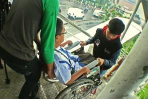 Menaiki tangga Jembatan Penyebrangan Orang (JPO). ( Tajuk.co / Aljon Ali Sagara )