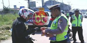 Salah seorang petugas kepolisian dari Polda Metro Jaya saat memeriksa pengendara motor yang terjaring razia di jalan Siliwangi, Pamulang kota Tangsel