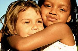 Black and white kids hug