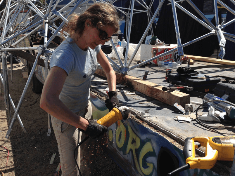 Wendy de Heer, a PhD student in psychology, uses an angle grinder on Dr. Brainlove's base. (Image courtesy of the Phage)