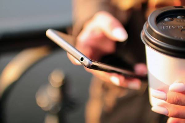 Hands holding a smartphone and a paper coffee cup