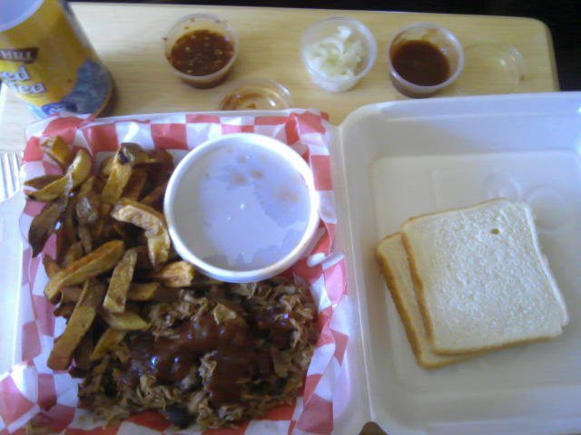 A styrofoam container with pulled pork, French fries, a cup of baked beans and two pieces of white bread