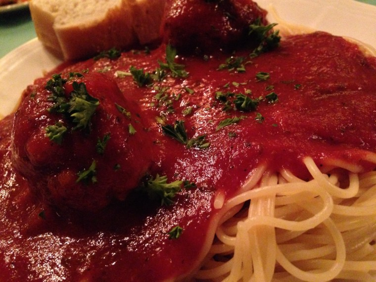 A large plate of spaghetti covered in marinara sauce