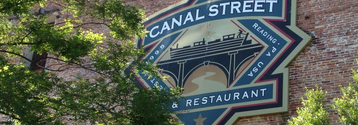 The exterior of Canal Street Pub features a large sign with their logo: a bridge over the Schuylkill River