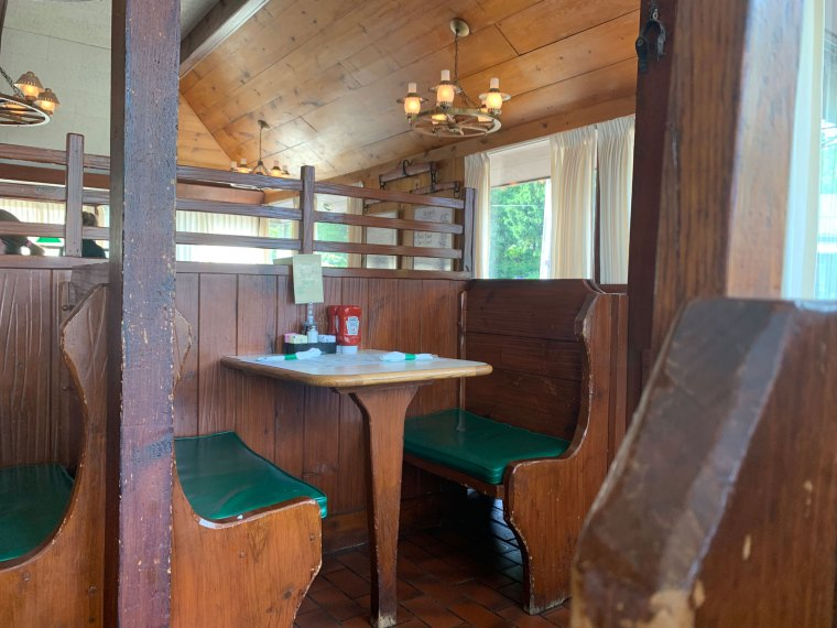 The dining room looks tired and worn with green cushions and cream curtains accenting worn-out wooden booths
