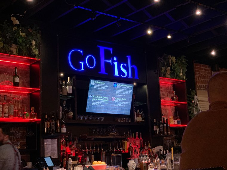 The bar area at Go Fish, complete with the restaurant's name in blue lights with red accent lighting on the shelves.