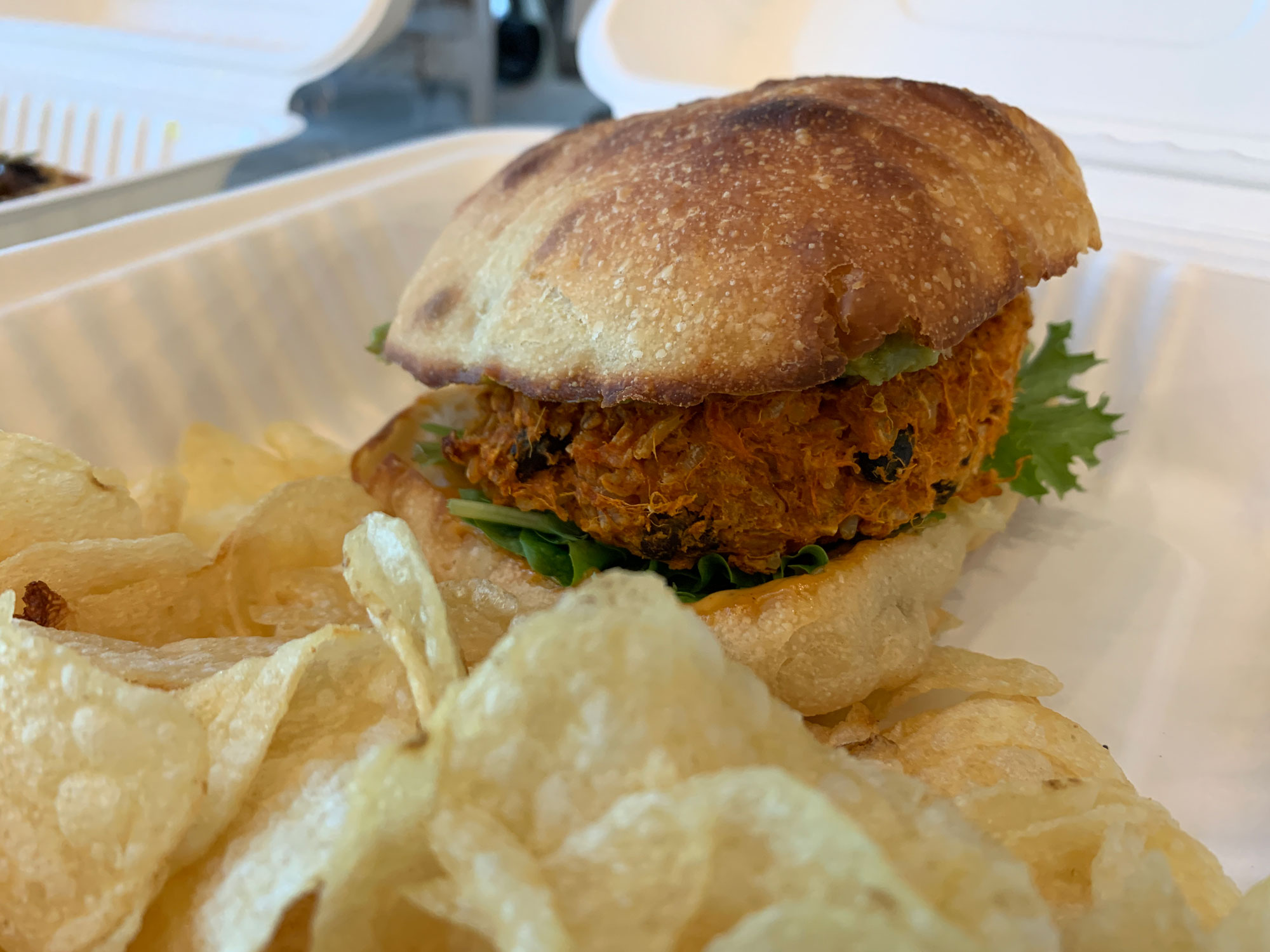 A vegan black bean and sweet potato burger with side of chips from Good Life Organics in Reading PA