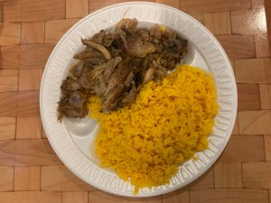Overhead view of paper plate with pulled pork and yellow rice from Latin Taste