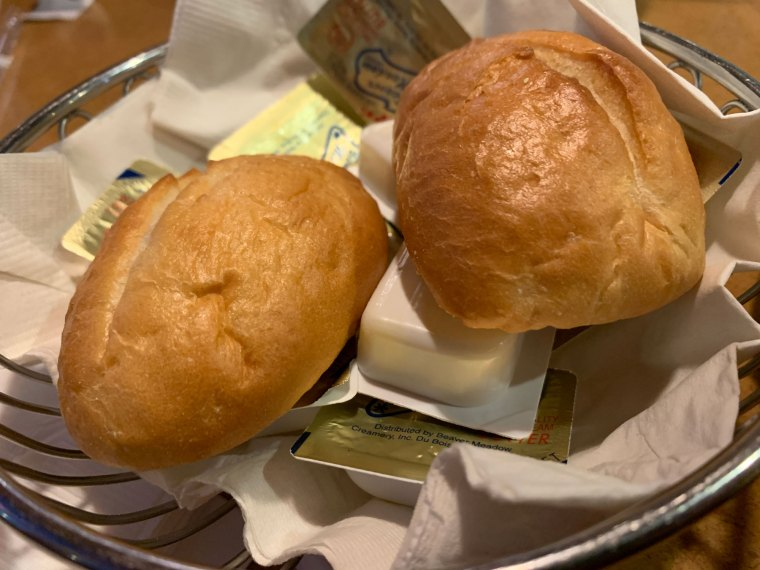 A pair of dinner rolls in a basket with 10 packets of butter