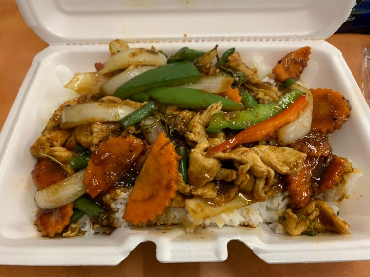A styrofoam container with a stir-fry, including chicken, carrot, green beans, onion and red and green bell peppers from Eve's Thai Kitchen
