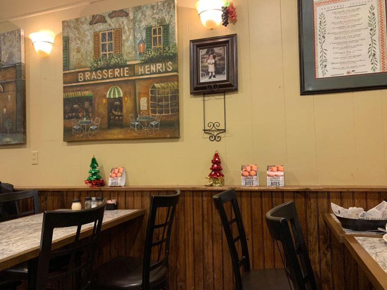 Tables along a wall decorated with generic images of Italy at Gino's Cafe in Shillington