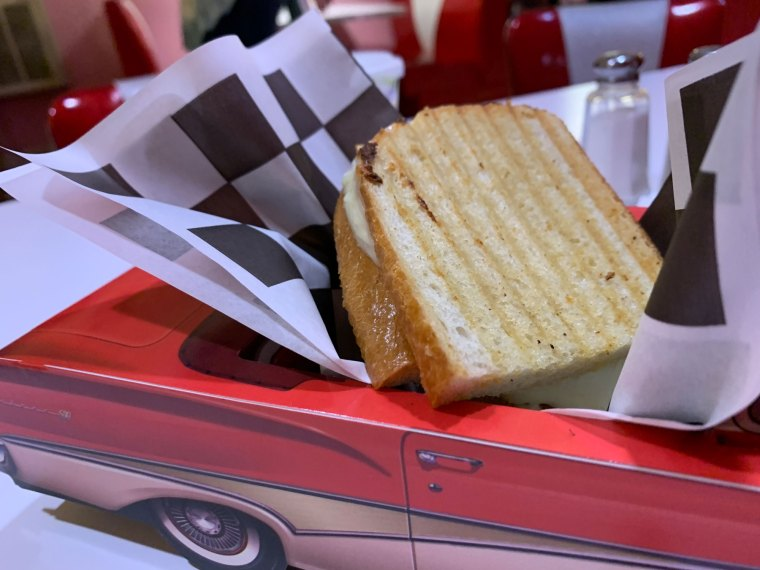 Close-up of Half a grilled cheese sandwich served in a 3D cardboard paper Ford Fairlane classic car