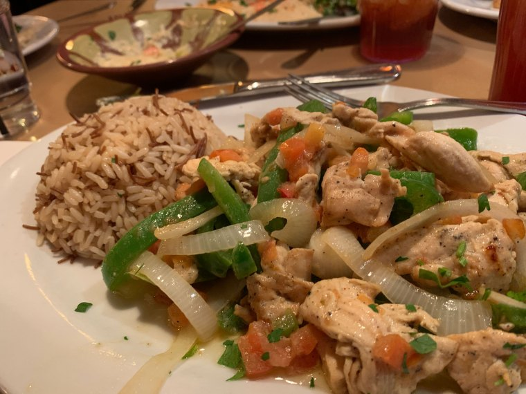 A plate with a stir-fry mix of chicken, green peppers, onions and tomatoes and a side of rice pilaf at Aladdin Mediterranean Restaurant