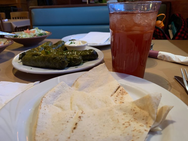 A plate with three thin pitas in the foreground with a glass of rose iced tea and a plate of stuffed grape leaves from Aladdin Mediterranean Restaurant