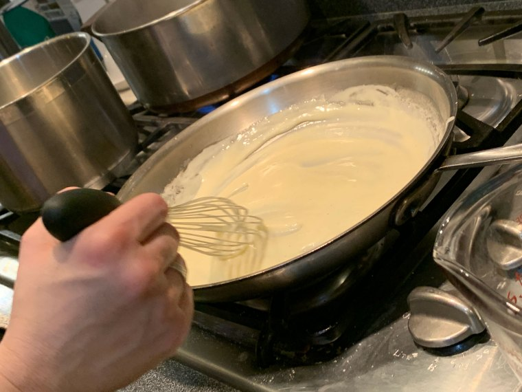 A hand whisks a cheese sauce for the gnocchi