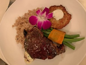 A plate with a filet Mignon, serving of mushroom risotto, seafood cake topped with lime ailoi, green beans and a purple flower from the Inn at Centre Park