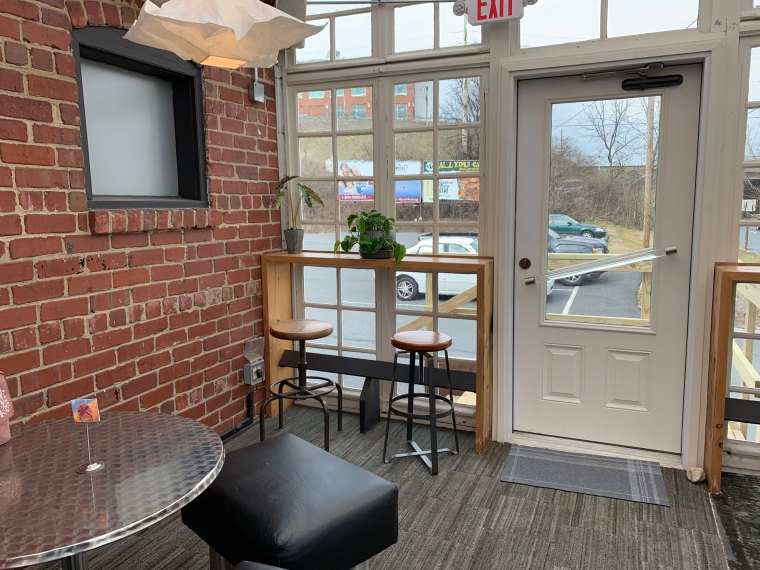 A look at the rear of the sun room at Greenhouse Cafe, including bench seats and a high-top table.