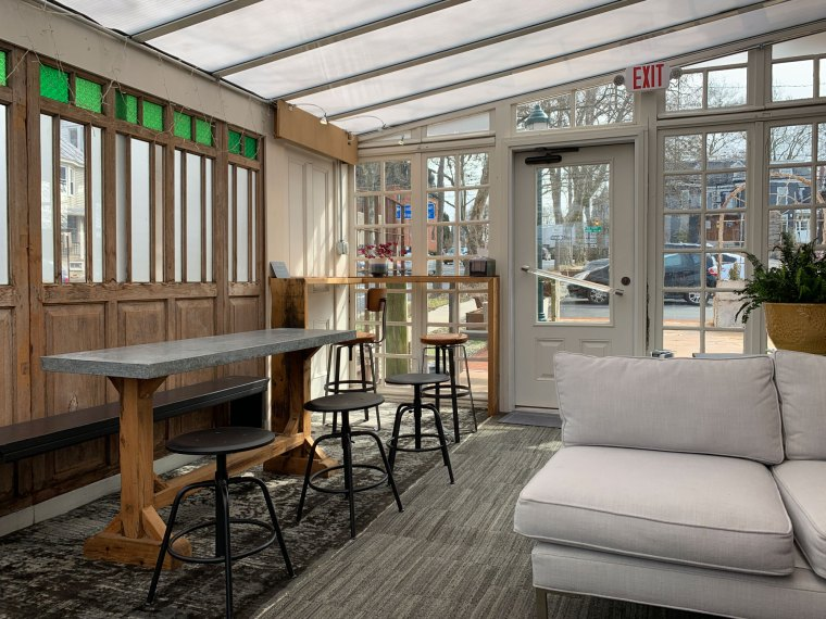 The interior of the sunroom dining area with high top tables and cushioned benches at the Greenhouse Cafe