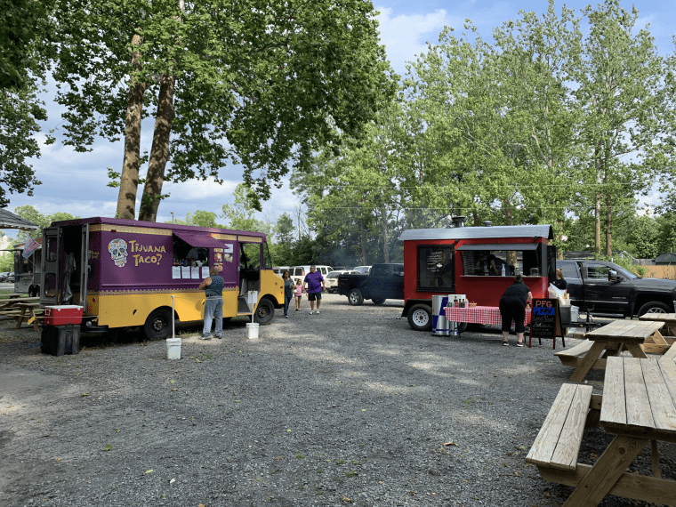 Food trucks parked on gravel with picnic tables in the foreground