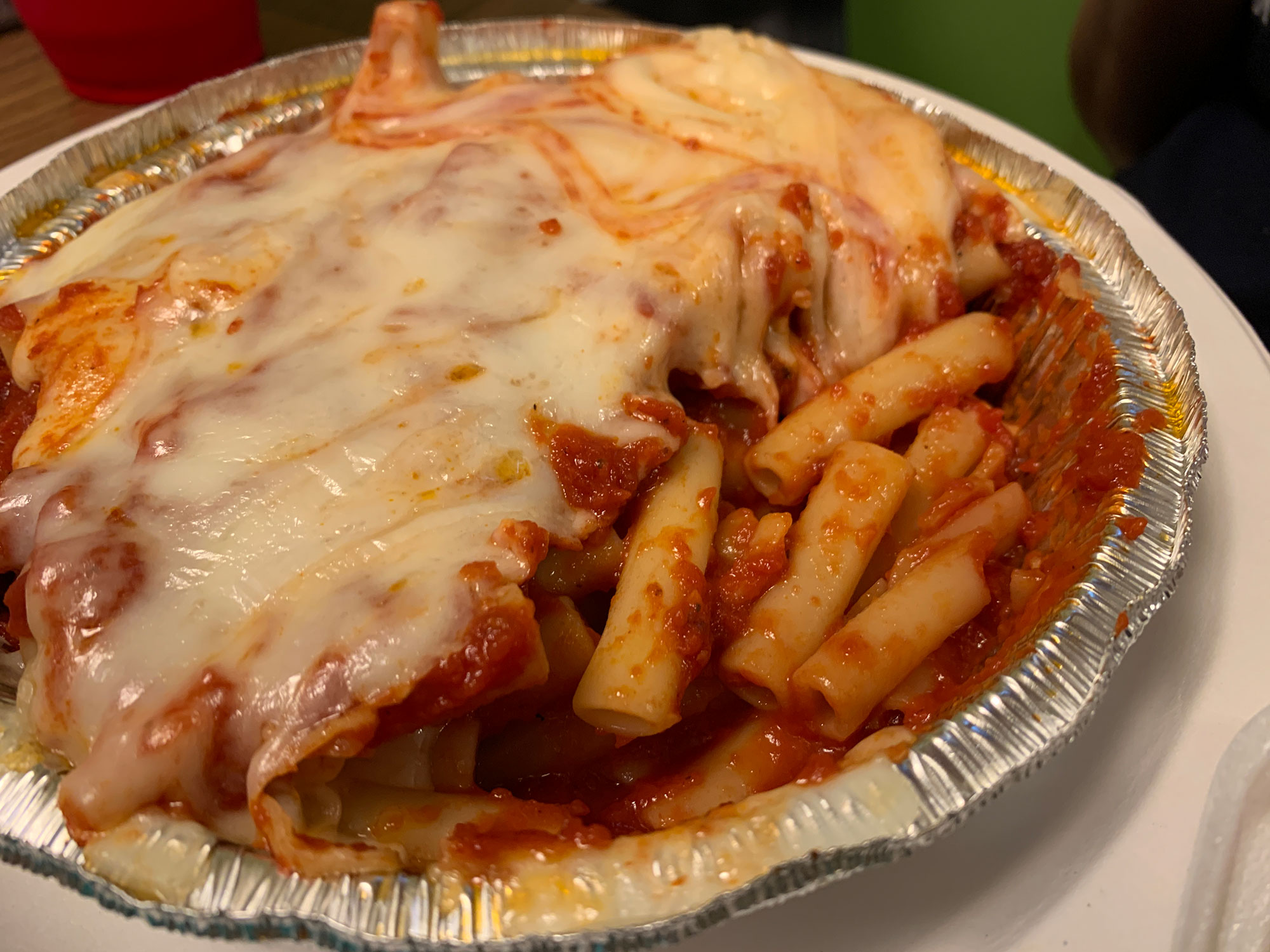 A round foil to-go container with baked ziti topped with cheese.