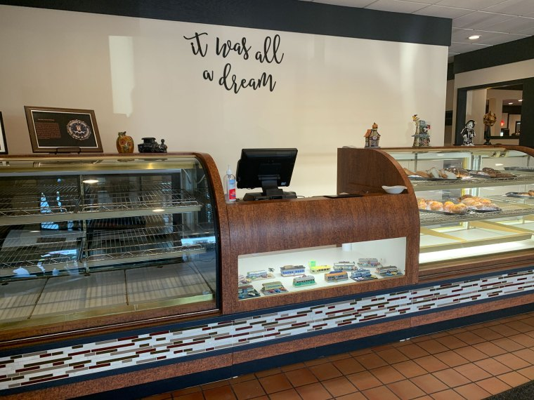 "A counter at a diner with a dessert display case and the phrase ""It was all a dream"" on the wall."