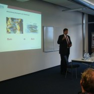 Bernd Wiest in a suit having a presentation in a room