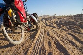 Opgewaaid zeer fijn zand over de weg in Turkmenistan