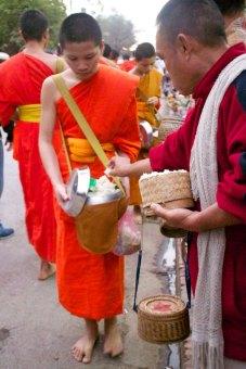 Dageraad in Luang Prabang, Laos. Monniken in de rij voor een handje rijst.