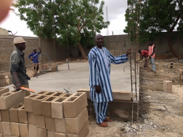 The foundation for the Steve Oubre Memorial house is done and walls are going up. Antony, the builder, is in stripes.