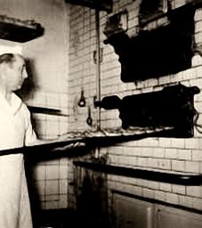 altes sw-Foto Bäcker schiebt Brote in den Ofen