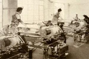 Buchbinderinnen arbeiten an Buchbindermaschinen