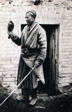 altes sw-Foto: Falkner in landestypischer Tracht mit Vogel auf der Hand