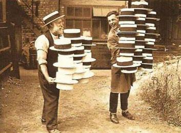 Foto: zwei Hutmacher mit einem Stapel Hüte