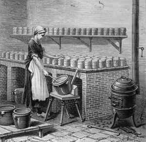 Frau in einer Käserei beim Herstellen von Camembert