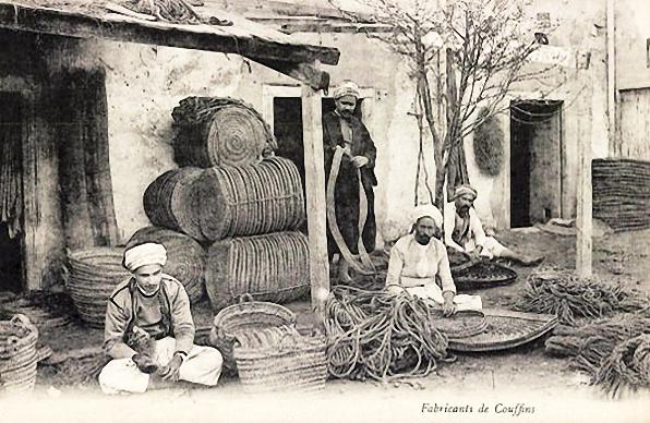 sw-Foto: indischer Korbmacher vor dem Haus sitzend